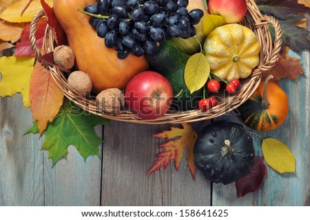 Fresh ripe pumpkins, apples, grape and nuts in wicker basket over wooden background  - stock photo