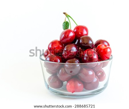 Fresh ripe red cherries with leaf on a glass bowl isolated on white background. They are fresh picked in Yakima Valley, a prime agricultural area of Washington State, US. Copy space.