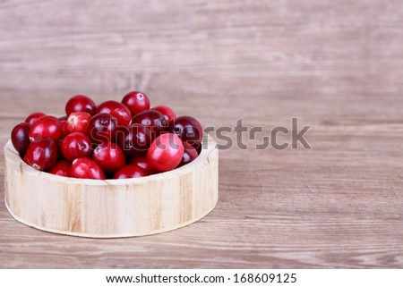 Fresh, ripe, red cranberries on a wooden background - stock photo