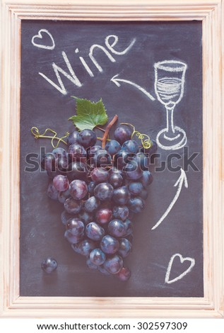 Fresh ripe red grape cluster on old chalk board. Toned photo. - stock photo