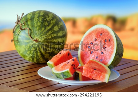 Fresh ripe red juicy watermelons and slices on a wooden table on autumn nature background. A healthy eco sweet food rich in vitamins. Popular product of organic farming. - stock photo