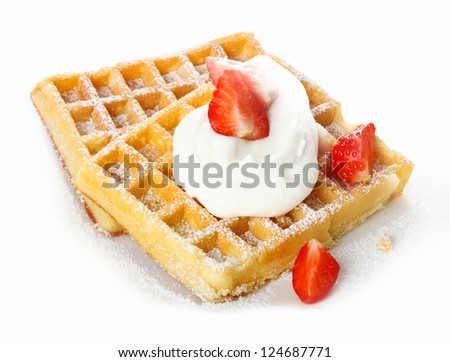 Fresh ripe red strawberries and whipped cream on a crisp golden waffle sprinkled with sugar for a refreshing dessert - stock photo