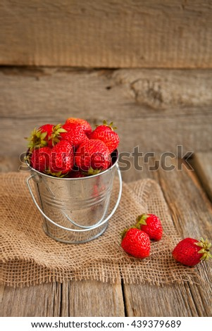 Fresh ripe red strawberries in a metal bucket on wooden table. - stock photo