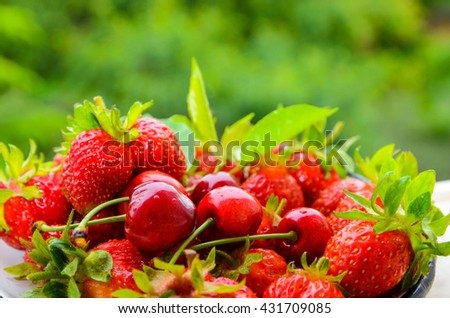 Fresh ripe strawberries and cherries on green trees background - stock photo