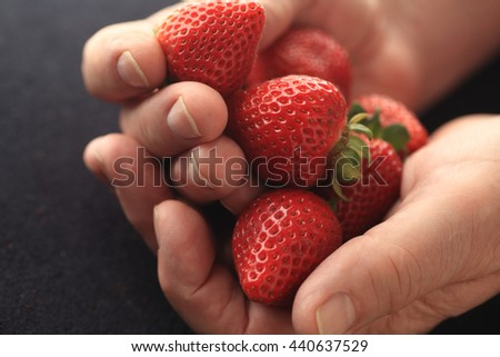 Fresh, ripe strawberries in a man's hands - stock photo