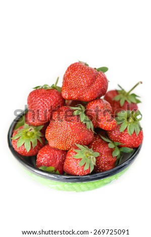 Fresh ripe strawberries in clay green bowl with a black strip, isolated on white background. Closeup. - stock photo