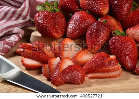 Fresh ripe strawberries sliced on a cutting board - stock photo