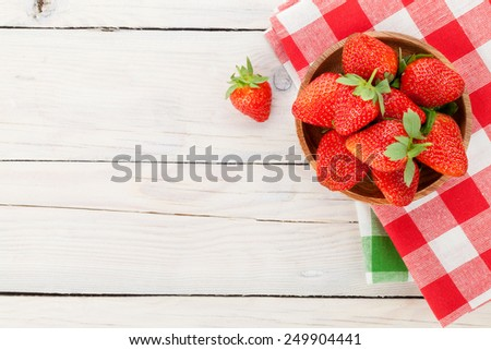 Fresh ripe strawberry in bowl over wooden table background. Top view with copy space - stock photo