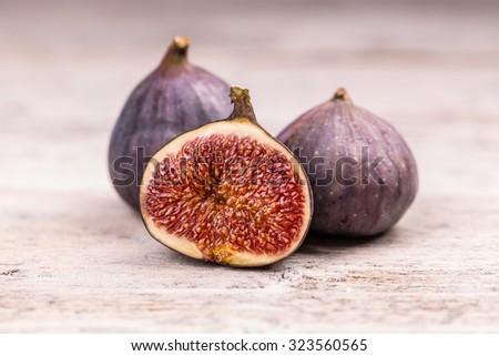 Fresh ripe sweet figs on white wooden background - stock photo