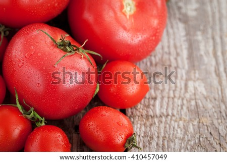 Fresh ripe tomatoes in a bag on wooden table - stock photo