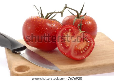 Fresh ripe tomatoes on a cutting board.