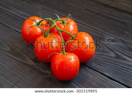 fresh, ripe tomatoes on wood background - stock photo
