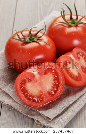 fresh ripe tomatoes with halfs on wood table - stock photo