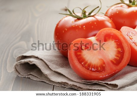 fresh ripe tomatoes with halfs on wood table, rustic style - stock photo