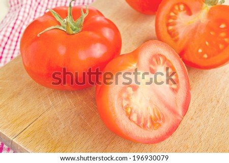 Fresh ripe tomatoes with halfs on wood table, tasty organic vegetable for healthy eating. - stock photo