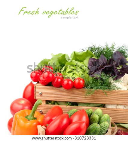 Fresh ripe vegetables in a wooden box on a white background with a place for the text. - stock photo