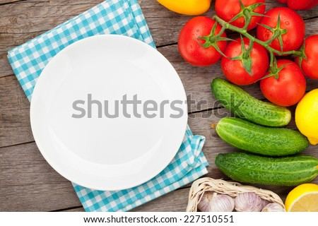 Fresh ripe vegetables on wooden table and empty plate with copy space - stock photo