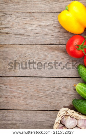 Fresh ripe vegetables on wooden table with copy space - stock photo