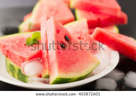 Fresh ripe watermelon slices and ice on black background, selective focus - stock photo