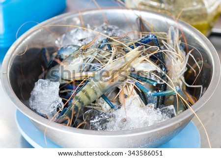Fresh river crayfish on the ice in bowl, prepare for sale - stock photo