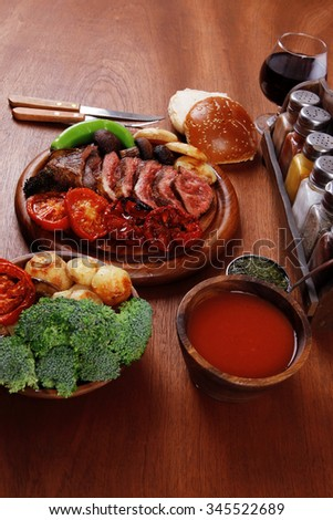 fresh roast bbq beef meat ribeye steak on wooden plate served with tomato juice in wooden cup, boiled broccoli, baked tomatoes potatoes, with white bun, and red wine glass on light walnut wooden table - stock photo