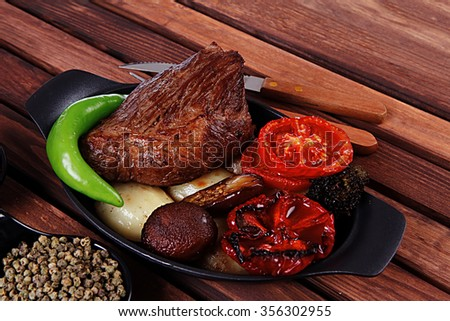 fresh roast bbq beef steak on black pan baked with mushroom potatoes tomatoes green hot chili pepper served with different peppercorn on dark wooden table - stock photo