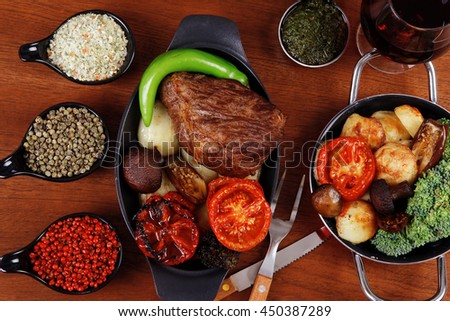 fresh roast beef meat rib eye steak with tomatoes,potatoes, hot chili pepper gern and pink peppercorn saucer, cutlery, set of spice, and red wine glass on light walnut table - stock photo