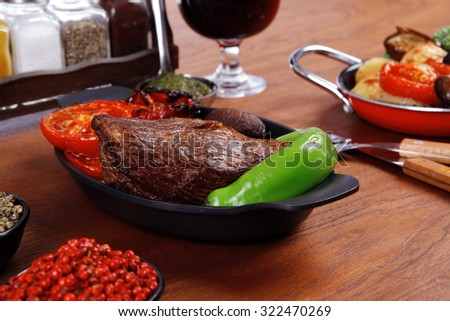 fresh roast beef meat rib eye steak with tomatoes,potatoes, hot chili pepper green and pink peppercorn saucer, cutlery, set of spice, and red wine glass on light walnut table - stock photo