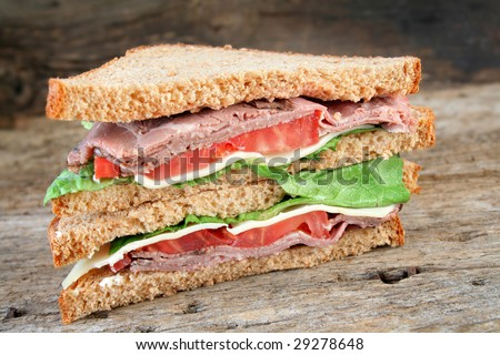 Fresh roast beef sandwich with swiss cheese, tomato, lettuce on rye bread with a wood textured background for a rustic look. - stock photo