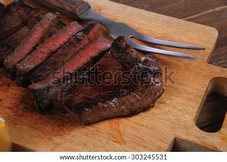 fresh roast red beef meat fillet mignon cutted on wooden plate with vintage fork many different kinds of dry spice over table - stock photo