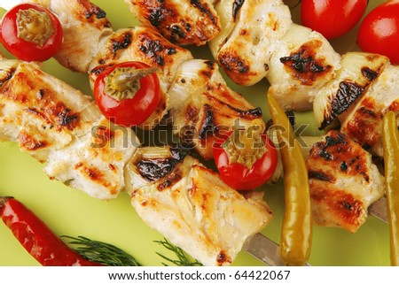 fresh roast shish kebab on green platter with vegetables - stock photo