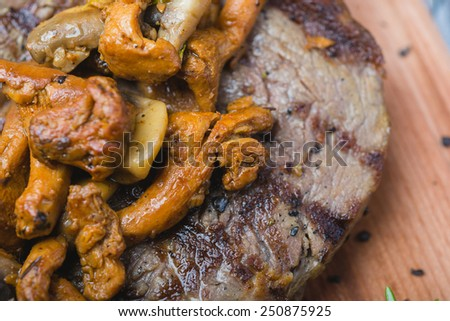 fresh roast tenderloin with mushrooms and potatoes on wooden plate with decoration on a wooden table in a restaurant - stock photo