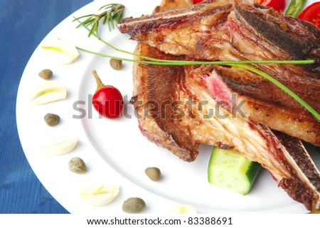 fresh roasted beef meat bone steak on ceramic dish with red hot pepper and tomatoes over blue wood table