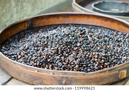 Fresh roasted coffee beans for sale in a flat round container at an outdoor market - stock photo