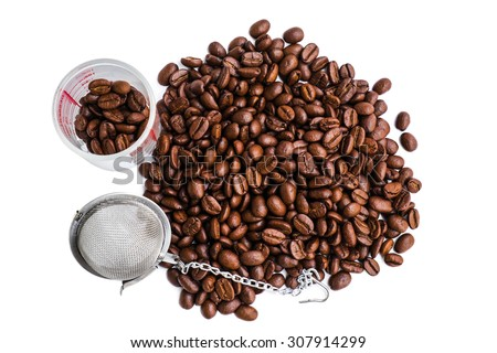 fresh roasted coffee beans with coffee shot glass and strainer - stock photo