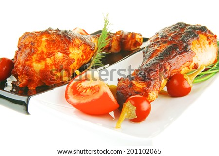 fresh roasted drumstick on ceramic plates with tomatoes - stock photo
