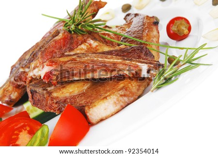 fresh roasted lamb meat fillet ready on china plate with tomatoes, green pepper , and garlic isolated  over white background