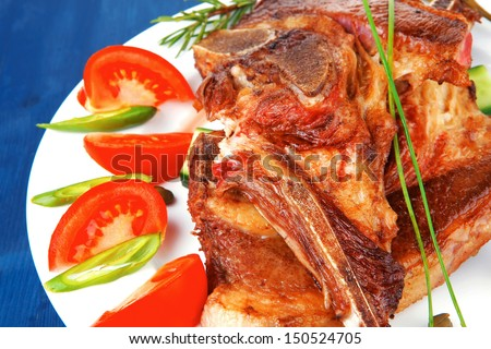 fresh roasted lamb meat fillet ready on china plate with tomatoes, green pepper , and garlic over blue wood table