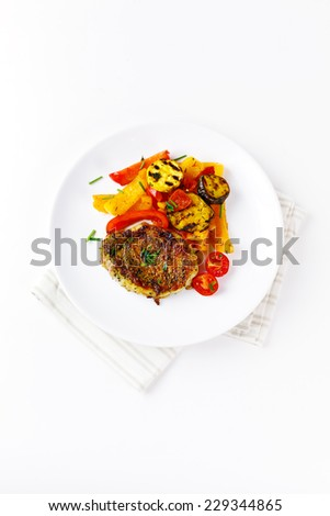 Fresh roasted pork meat steak served with grilled vegetables (orange and yellow pepper, eggplant, tomato, zucchini) and fresh chives over white background. Top view. - stock photo