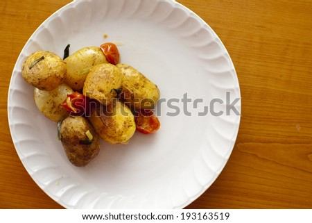 Fresh roasted potato with cherry on white dish top view - stock photo