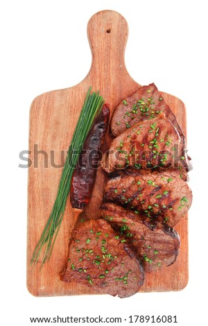 fresh roasted red meat with thyme and chives on wooden plate isolated on white background - stock photo