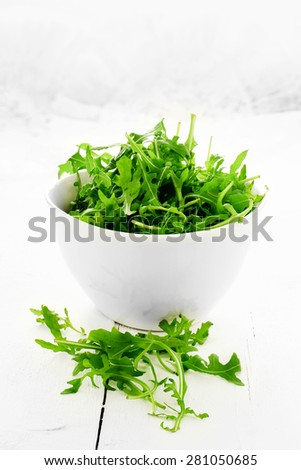 Fresh rocket salad leaf salad against a white, light, background. Concept image for healthy eating. Copy space. - stock photo