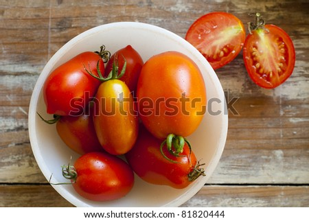 Fresh Roma and Juliet tomatoes, picked fresh from the garden, grouped in a white bowl.