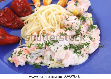 fresh rose wild salmon baked in cream cheese sauce with italian pasta and red hot pepper on blue plate isolated over white background high resolution - stock photo