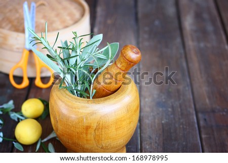 fresh rosemary and sage herbs in wooden pestle and mortar. natural light. - stock photo