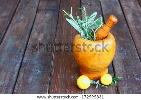 fresh rosemary herbs in wooden pestle and mortar on wooden table  - stock photo