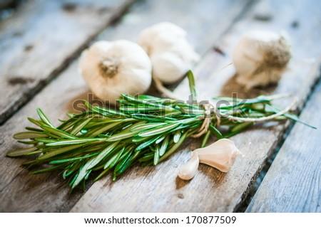 Fresh rosemary with fresh garlic on wooden background - stock photo