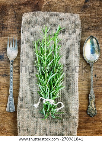 Fresh rosemary with tag on rustic wooden background - stock photo