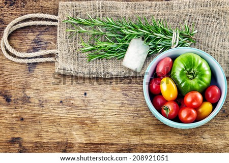 Fresh rosemary with tag, red and green tomatoes on rustic wooden background - stock photo