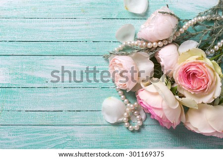 Fresh roses flowers and pearl on turquoise painted wooden background. Selective focus. Place for text. - stock photo